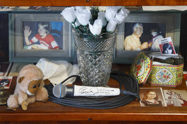 FILE - This Thursday, Nov. 21, 2019, file photo shows a signed microphone by The Who's Roger Daltrey on display in a memorial cabinet at the Finneytown High School secondary campus in Finneytown, Ohio, along with other mementoes of the three Finneytown students killed in a stampede at the band's 1979 Cincinnati concert. Every year, Finneytown alumni hold a memorial scholarship fundraising event to honor their three classmates. In 2020, because of the coronavirus, they organized a show of prerecorded video interviews with The Who's frontman, Roger Daltrey, guitarist-songwriter Pete Townshend and a mix of recorded and live discussions with relatives of the 11 people killed on Dec. 3, 1979. (AP Photo/John Minchillo, File)