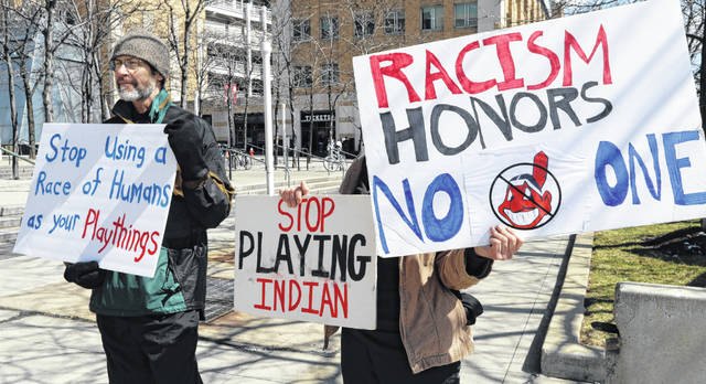"FILE - James Watson, left, protests before a baseball game between the Chicago White Sox and the Cleveland Indians, Monday, April 1, 2019, in Cleveland. The Cleveland Indians are changing their name _ they just don't know to what or when. Expressing that ""it's time,"" team owner Paul Dolan said that after months of internal discussions and meetings with groups, including Native Americans who have sought to have the team stop using a moniker many deem racist, the American League franchise is dropping the name it has been known by since 1915. In an exclusive interview with The Associated Press on Monday, Dec. 14, 2020, Dolan said: ""The name is no longer acceptable in our world.""(AP Photo/Tony Dejak, File)"