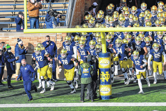 Notre Dame Fighting Irish head coach Brian Kelly leads his players out of the tunnel before an NCAA college football game Saturday, Dec. 5, 2020, in South Bend, Ind. (Matt Cashore/Pool Photo via AP)