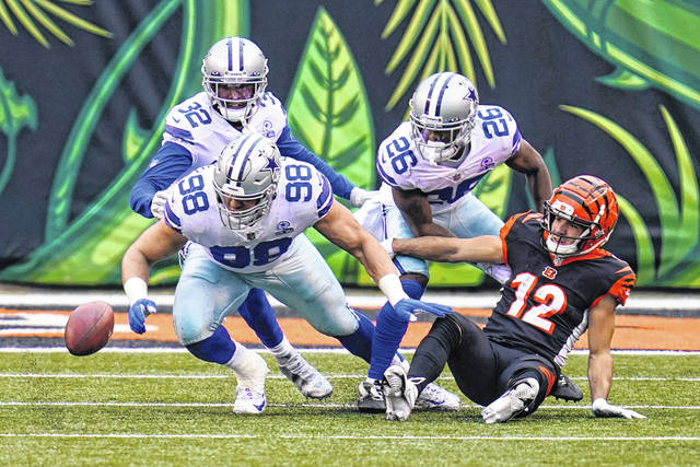 Cincinnati Bengals wide receiver Alex Erickson (12) fumbles the ball in the first half of an NFL football game against the Dallas Cowboys in Cincinnati, Sunday, Dec. 13, 2020. The Cowboys recovered. (AP Photo/Bryan Woolston)