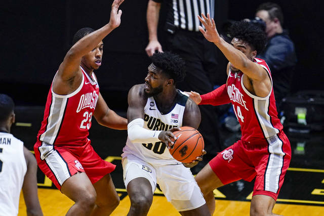 Ohio State center Zed Key (23) and forward Justice Sueing (14) defend Purdue forward Trevion Williams (50) during the first half of an NCAA college basketball game in West Lafayette, Ind., Wednesday, Dec. 16, 2020. (AP Photo/Michael Conroy)