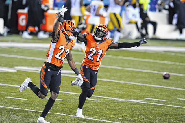 Cincinnati Bengals' William Jackson (22) and Mackensie Alexander (21) celebrate after Pittsburgh Steelers turned the ball over on downs during the second half of an NFL football game, Monday, Dec. 21, 2020, in Cincinnati. (AP Photo/Michael Conroy)