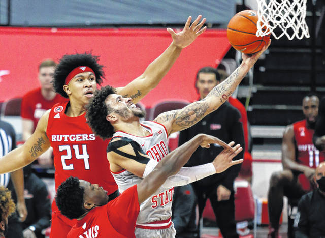 Ohio State guard Duane Washington, right, goes up for a shot against Rutgers guard Ron Harper, top, and guard Montez Mathis during the first half of an NCAA college basketball game in Columbus, Ohio, Wednesday, Dec. 23, 2020. (AP Photo/Paul Vernon)