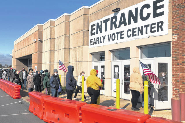 People bundled against the cold stand in a slowly moving line Oct. 30 to cast early votes at the Franklin County Board of Elections in Columbus.