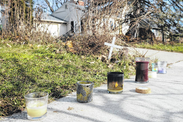 A small set of candles sit on a sidewalk near the site of a fatal police shooting Wednesday on Oberlin Drive in Columbus. Body camera footage released Wednesday shows Andre Hill, a 47-year-old Black man, emerging from a garage and holding up a cellphone in his left hand seconds before he is fatally shot by a Columbus police officer.