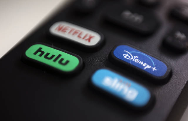 FILE - In this Aug. 13, 2020 file photo, the logos for Netflix, Hulu, Disney Plus and Sling TV are pictured on a remote control in Portland, Ore.  As movie theaters closed and lockdowns descended across the country, people turned to the ever-growing number of video streaming services for entertainment.  (AP Photo/Jenny Kane)