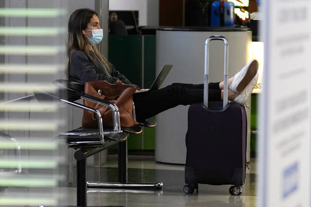 FILE - A traveler wears a mask as she waits for her flight in Terminal 3 at O'Hare International Airport in Chicago, Sunday, Nov. 29, 2020.  The coronavirus pandemic created winners and losers in the business world. Wall Street recovered after March, even though Main Street is still struggling.  As few people traveled, the airline industry needed billions of dollars in aid from the government and is still threatening to lay off workers.(AP Photo/Nam Y. Huh)