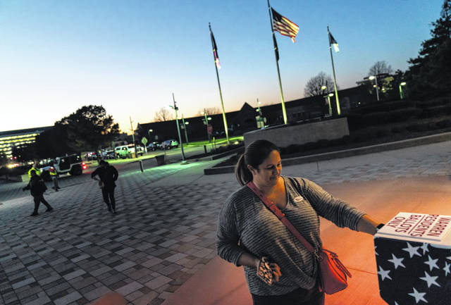 Wendy Gill inserts her absentee ballot at a drop-off box Nov. 3 as the sun sets on Election Day outside City Hall in Warren, Mich. The pandemic triggered wholesale changes to the way Americans voted in 2020, but that's no guarantee measures making it easier to cast ballots will stick around for future elections.