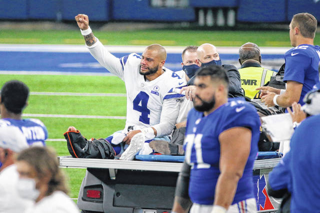 FILE - In this Oct. 11 , 2020, file photo, Dallas Cowboys quarterback Dak Prescott (4) lifts his fist to cheers from fans as he is carted off the field after suffering an injury during the second half of the team's NFL football game against the New York Giants in Arlington, Texas. Prescott was off to a fast start, becoming the first player in NFL history to pass for at least 450 yards in three straight games. But he suffered a compound fracture and dislocated right ankle against the Giants and missed the rest of the season. (AP Photo/Michael Ainsworth, File)