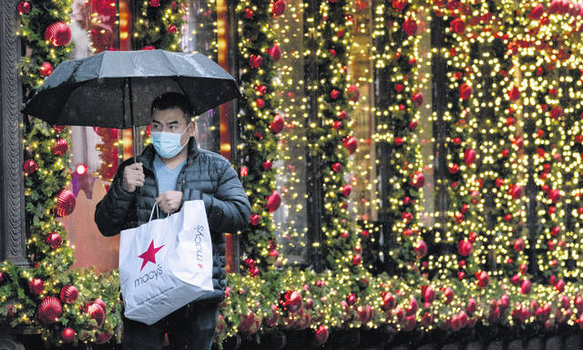 A shopper walks by a holiday window display in New York on Nov. 30. Many of us won't be celebrating the holidays with our families this year, so gift-giving might feel like the best way to show love from afar. And while shoppers are planning to spend less this year than last, according to a NerdWallet survey, more are also planning to use credit cards to purchase gifts.