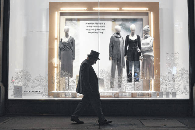 A man walks past a closed shop on Regent Street in central in London, Sunday, Dec. 20, 2020. Millions of people in England have learned they must cancel their Christmas get-togethers and holiday shopping trips. British Prime Minister Boris Johnson said Saturday that holiday gatherings can't go ahead and non-essential shops must close in London and much of southern England. Johnson imposed a new, higher level of coronavirus restrictions to curb sharply spreading infections in the capital and other areas.