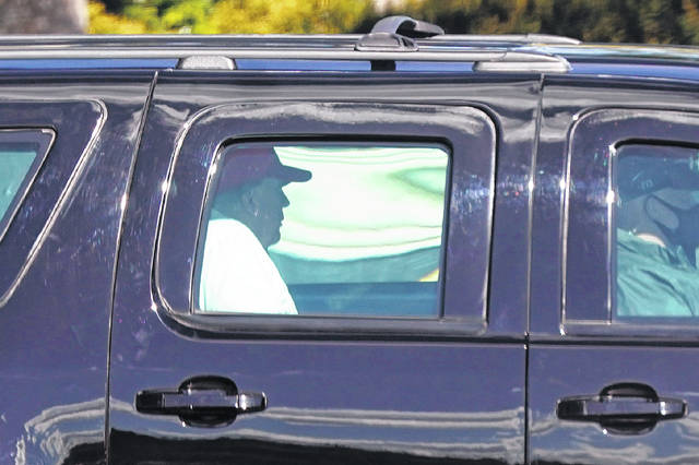 President Donald Trump rides in a motorcade vehicle as he departs Trump International Golf Club on Sunday in West Palm Beach, Fla.