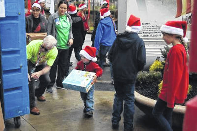 Shown are Tyler Slaven's family and others unloading toys last year.