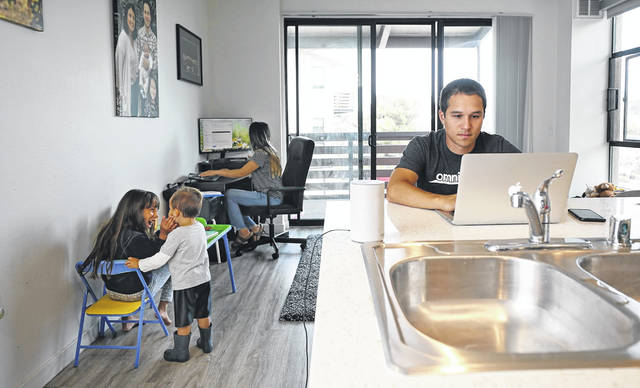 Lucas Fernandez, of La Mesa, Calif., is working a hybrid model where he works at home part of the time and at the office other times. His wife, Deicy, is also working from home, and the two do so while watching their children, Vienna, 7, and Lucas Jr., 2.