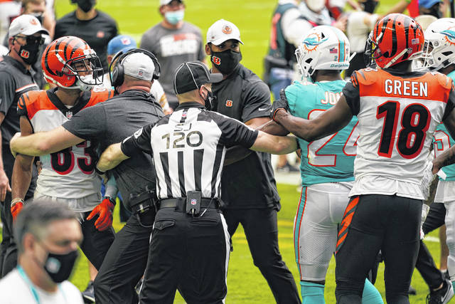 NFL side judge Jonah Monroe (120) and Cincinnati Bengals coaches attempt to stop a fight on the field during the first half of Sunday's game between the Bengals and the Miami Dolphins on Sunday.