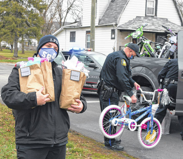 Lima police officers helped distribute Christmas presents to children on Saturday as part of the Cops and Kids program.
