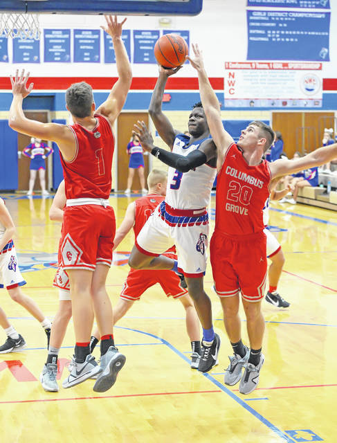 Crestview's Rontae Jackson puts up a shot against Columbus Grove's Bo Birnesser, left, and Ethan Halker during Friday night's game at Crestview.