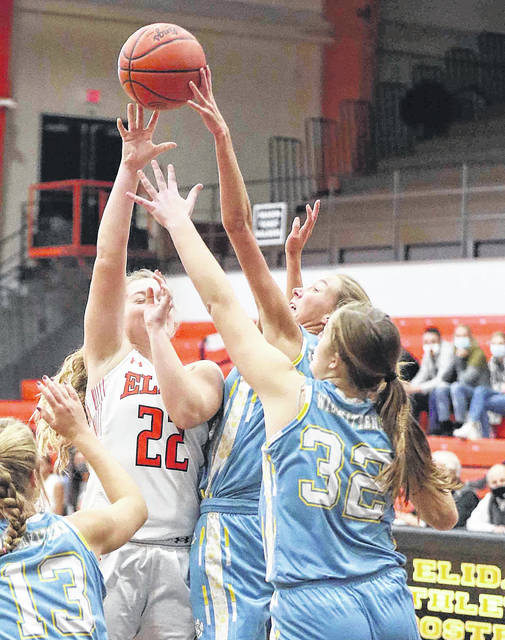 Elida's Ayton Kuhn shoots over Bath's Ruby Bolon (23) and Anne Oliver (32) in the second quarter at Elida field house Thursday.
