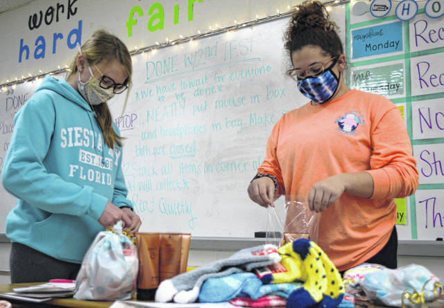 Isabelle Gibson and Leila Hannouz, eighth-graders at Elida Middle School, help prepare care packages for seniors at Shawnee Manor Nursing Home.