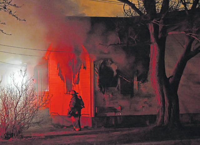 A Perry Township Fire Department firefighter works at a house fire at 1559 Bowman Road around 4:30 a.m. Thursday morning.
