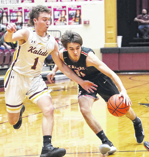 Spencerville's Dylan Smith tries to dribble around Kalida's Ayden Warnecke during Saturday night's game at Kalida.