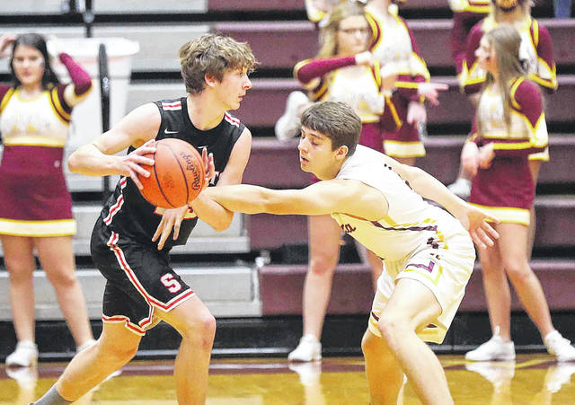 Kalida's Justin Siebeneck tries to make a steal against Spencerville's Tyler Koenig during Saturday night's game at Kalida.