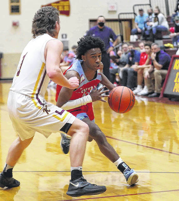 Lima Central Catholic's DeMarr Foster tries to drive around Kalida's Ayden Warnecke in the first quarter at Kalida Friday.