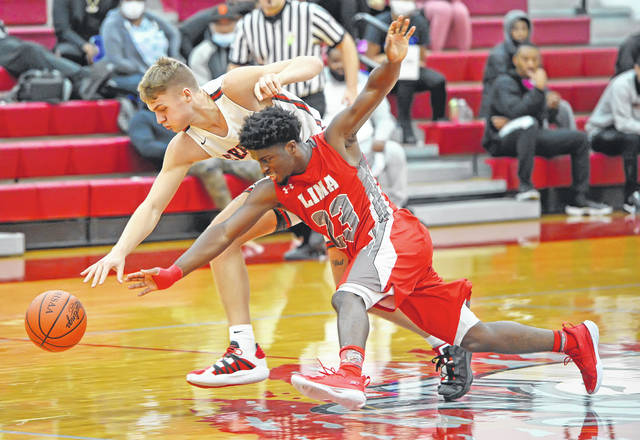 Lima Senior's Jourdyn Rawlins and Shelby's TJ Pugh compete for a loose ball during Sunday's Coach Q Holiday Classic at Lima Senior High School.