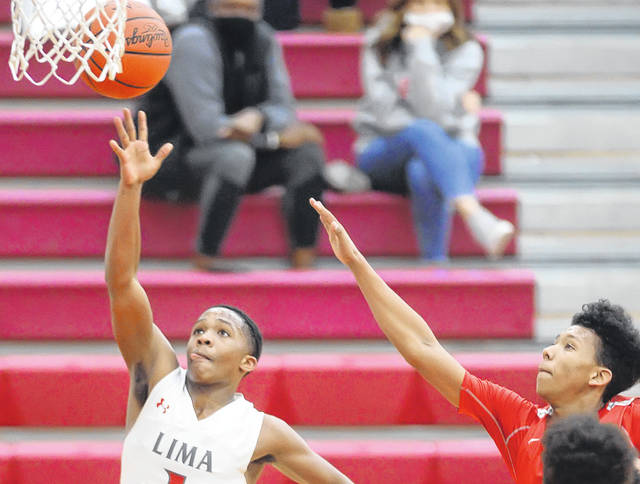 Lima Senior's Khalil Luster goes in for the lay up against Toledo Central Catholic's Micah Thames during Tuesday's game at Lima Senior High School.