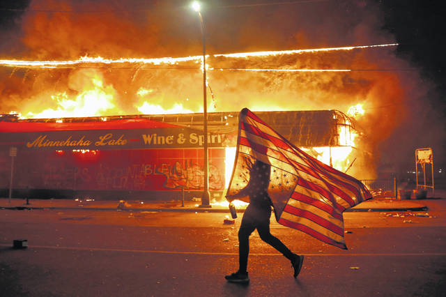 A protester carries a U.S. flag upside down as he walks past a burning building in Minneapolis on May 28, 2020, during a protest over the death of George Floyd, a Black man who died after a white Minneapolis police officer pressed a knee into his neck for several minutes.