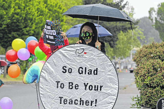 """FILE - Han-Yin Hsu, who teaches design at Tacoma School District's IDEA (Industrial Design, Engineering and Art) High School, holds a sign that reads """"So Glad To Be Your Teacher,"""" as she greets students during a drive-up car parade to distribute caps and gowns to seniors graduating from the school, on May 12, 2020. All high schools in the district held virtual graduation ceremonies, so the event, which required students to stay in their cars, allowed them to be greeted by cheering teachers and administrators one more time before graduation. (AP Photo/Ted S. Warren, File)"""
