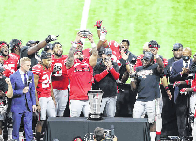 Ohio State's Haskell Garrett holds up the Big Ten championship trophy after the Buckeyes defeated Northwestern in the conference championship game Saturday at Lucas Oil Stadium in Indianapolis. See more game photos at LimaScores.com.