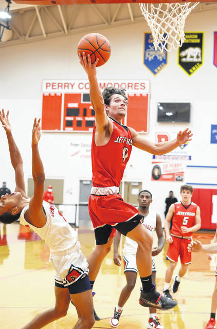 Delphos Jefferson's Ian Wannemacher puts up a shot against Perry's Jefferey Simpson during Saturday night's game at Perry.