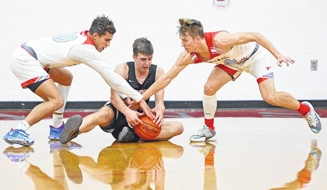Lima Central Catholic's Rossy Moore, left, and Evan Unruh, right, attempt to steal the ball from Ashland's Eli White during Sunday's Coach Q Holiday Classic at Lima Senior High School.