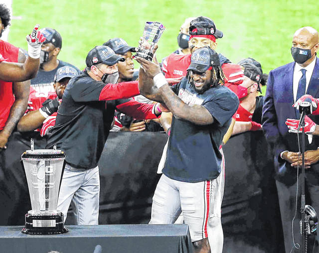 Ohio State running back Trey Sermon (right) celebrates with Ohio State coach Ryan Day (left) after winning the MVP award in the Big Ten football championship game on Saturday. Sermon ran for an Ohio State record 331 yards in a 22-10 win over Northwestern.