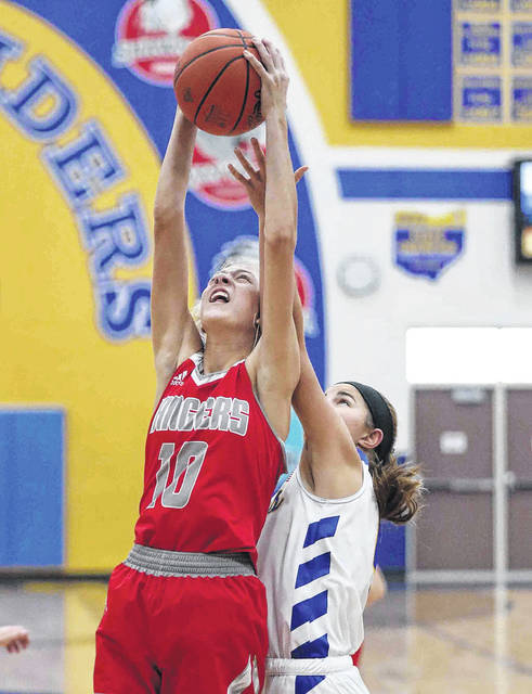 New Knoxville's Carsyn Henschen pulls down a rebound against Saint Marys' Elena Menker during Saturday's game at at St. Marys. See more game photos at LimaScores.com.