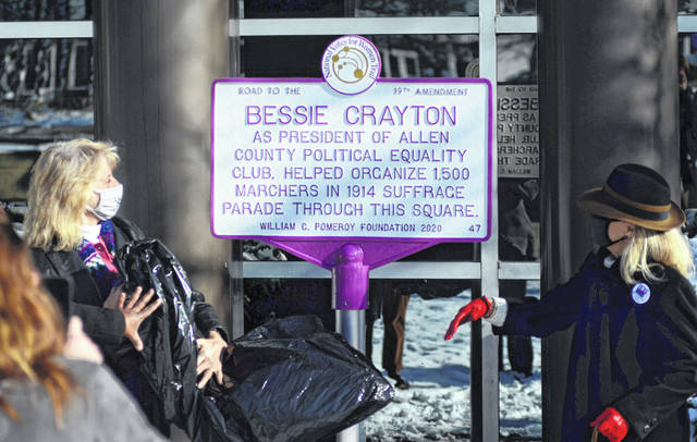 League of Women Voters members Candy Newland, left, and Shannon Quinn unveil the white-and-purple plaque honoring local women's suffrage leader Bessie Crayton to a crowd of onlookers Wednesday.