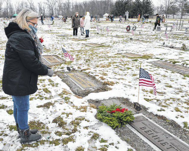 Nancy Rader stands over the grave of her father, Gail Bennett, a veteran who fought in World War II.