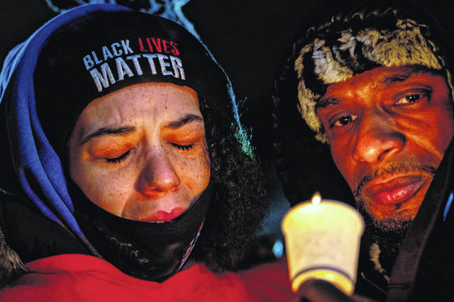 """Karissa Hill, daughter of Andre Hill, reacts during a vigil being held for her father at Brentnell Community Recreation Center in Columbus. Records released Tuesday provided new details into the Dec. 22 shooting by Columbus Police Officer Adam Coy, who is white. The city fired Coy on Tuesday, accusing him of incompetence and """"gross neglect of duty,"""" among other charges. Ohio, The police chief of Columbus, Ohio, recommended on Thursday, Dec. 24, 2020, that the officer who shot and killed Hill, a 47-year-old Black man, earlier this week be fired. (Gaelen Morse/The Columbus Dispatch via AP)"""