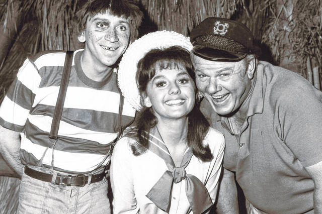 """In this 1965 file photo, Dawn Wells, center, poses with fellow cast members of """"Gilligan's Island,"""" Bob Denver and Alan Hale Jr., in Los Angeles. Wells, who played the wholesome Mary Ann on the 1960s sitcom """"Gilligan's Island,"""" has died of causes related to COVID-19."""