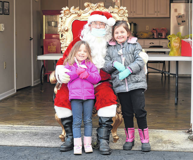 Daphne Spencer, 4, and Sophia Spencer, 7, get a hug from Santa during Sunday's drive-by Santa at the Pure Oil Station in Lafayette.