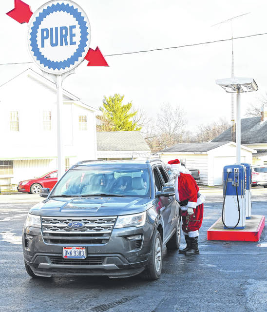 Santa greets children during Sunday's drive-by Santa at the Pure Oil Station in Lafayette.