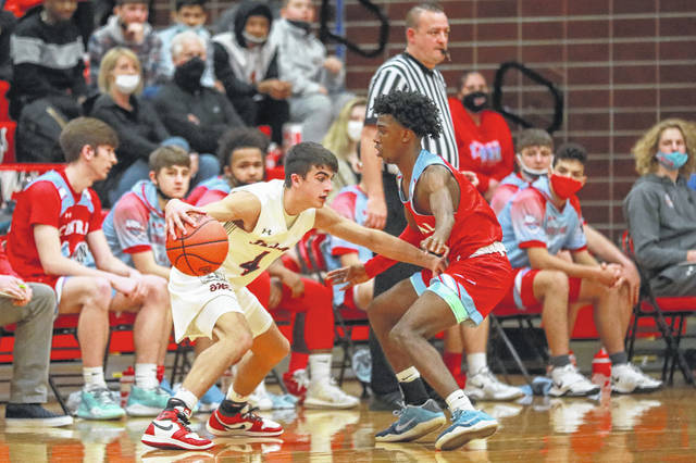 Shawnee's Brady Wheeler looks to drive past Lima Central Catholic's DeMarr Foster in Wednesday crosstown rivalry game.