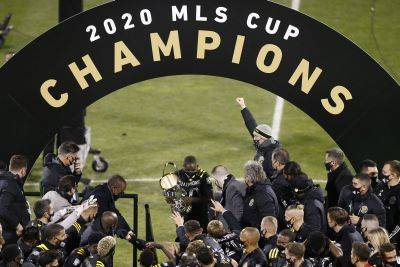 Columbus Crew's Jonathan Mensah, center, holds the MLS Cup after the Crew defeated the Seattle Sounders 3-0 in the championship game Saturday in Columbus. (AP photo)