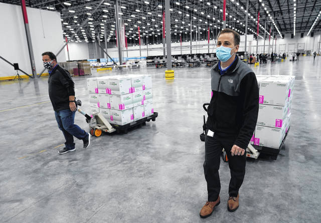 Boxes containing the Moderna COVID-19 vaccine are moved to the loading dock for shipping at the McKesson distribution center in Olive Branch, Miss., Sunday, Dec. 20, 2020.