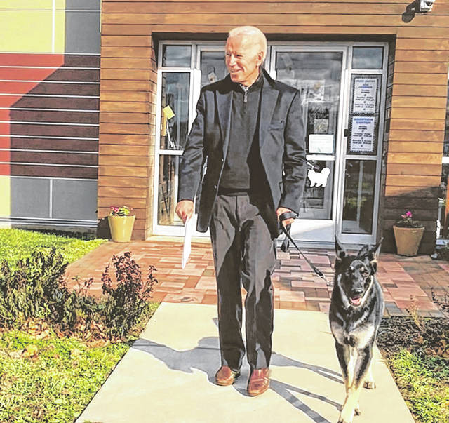 Joe Biden is shown leaving the Delaware Humane Association two years ago with his newly-adopted German shepherd Major. The president-elect will likely wear a walking boot for the next several weeks as he recovers from breaking his right foot while playing with Major on Saturday.
