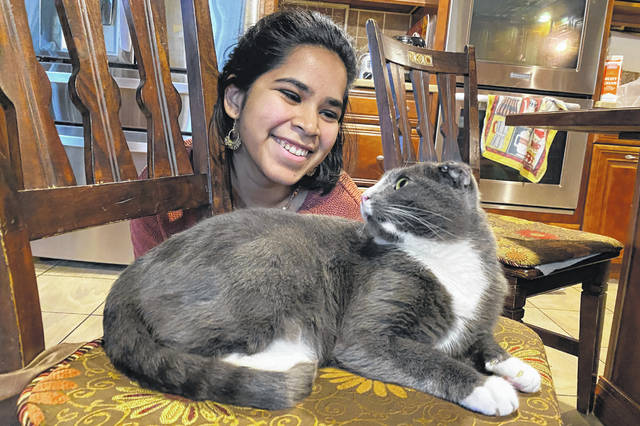 """Devika Ranjan smiles at her cat, Aloo, , in Andover, Mass. The formerly feral cat is believed to be around 3, and seems to be very comfortable with a slow-paced, high-attention pandemic life. """"My working from home, I think he loves it,"""" she says. """"I think he is just ready to settle down in life. If he were human, he'd probably sit on the couch with a PBR (beer) and watch TV all day."""""""