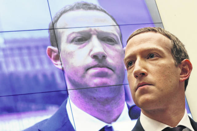 With an image of himself on a screen in the background, Facebook co-founder and CEO Mark Zuckerberg testifies before the House Financial Services Committee on Capitol Hill in 2019.