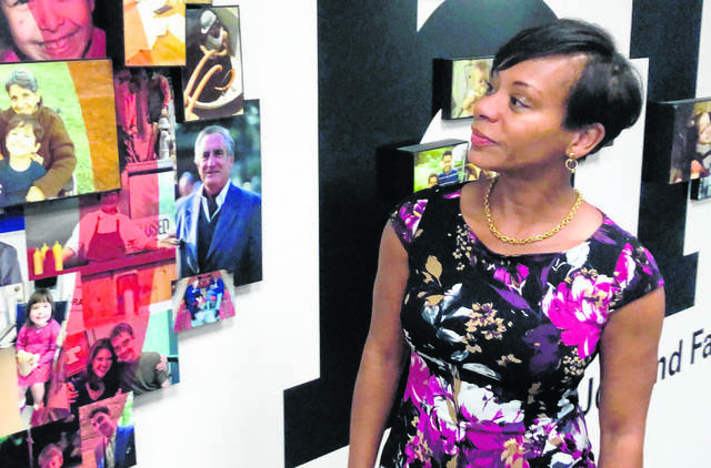 FILE - In this Aug. 15, 2019 file photo Kimberly Hall, director of the Ohio Department of Job and Family Services, looks over a photo display outside her office, in Columbus, Ohio. A federal lawsuit has been filed seeking to force Ohio to increase the amount of child support payments it provides to people who have taken custody of children they're related to.