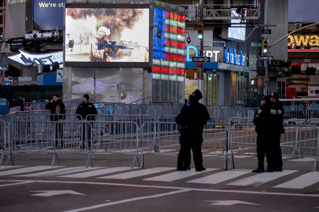 Police officers stand along a mostly empty Seventh Avenue during what would normally be a Times Square packed with people in New York late Thursday. Celebrations were truncated this New Year's Eve due to the ongoing pandemic.